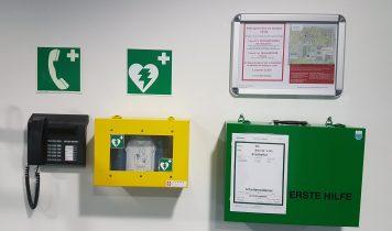 An der Wand hängen ein Notruftelefon, ein Erste Hilfe Koffer, Ein Defibrilator und eine Liste der Ersthelfer mit ihren Telefonnummern. Alles gut gekennzeichnet mit den richtigen Schildern.