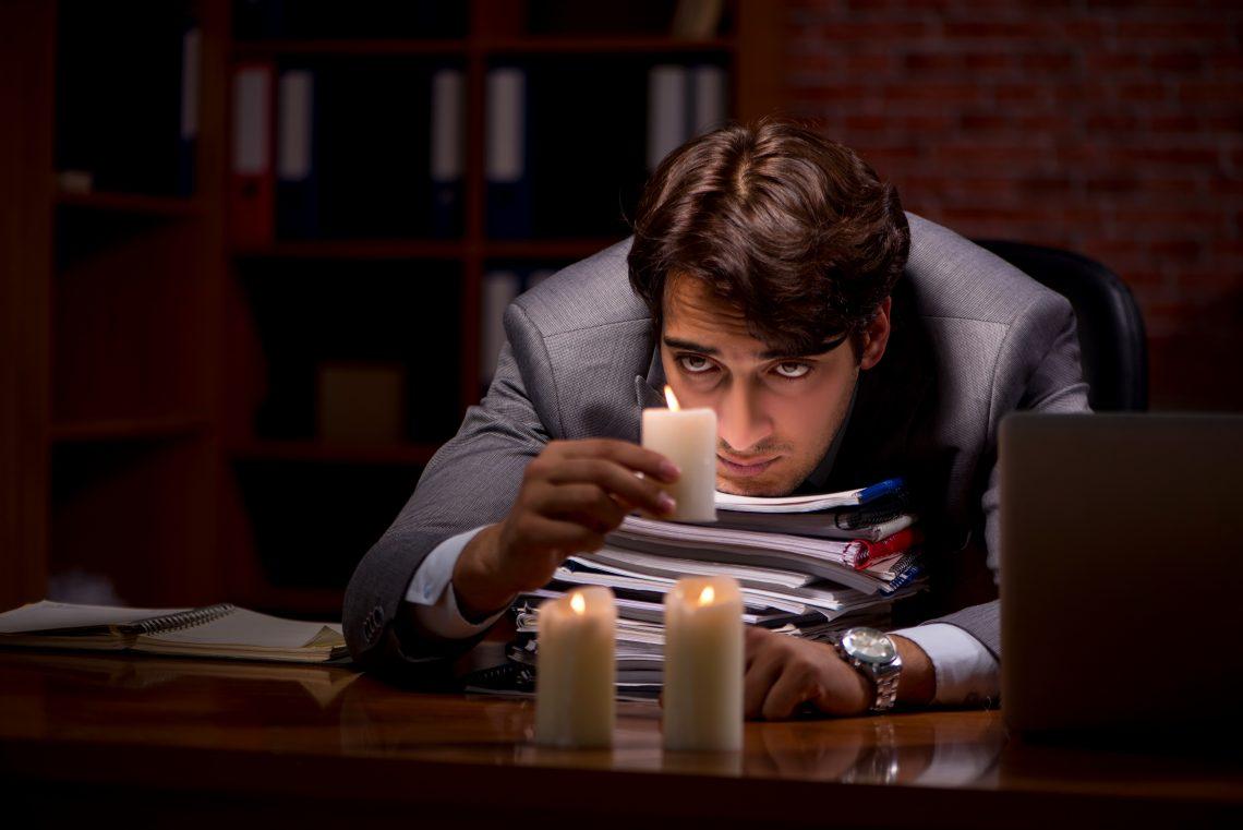 Geschäftsmann, der spät im Büro mit Kerzenlicht arbeitet