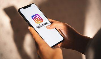 Frau hält Handy mit Logo der Instagram-Anwendung in ihrer Hand