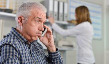 verzweifelter älterer Mann mit Handy in der Hand